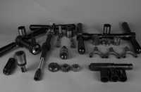 LAN71 Tool Assemblage.  All tools aside from the Marchetti bottom bracket taps are designed and machined in the Strawberry workshop.  The cutters are blanked out, heat treated and then precision ground in Portland.  All grinding is performed by McKenzie Tool Grinding in Portland.  The wishbone castings are a Strawberry design and the castings are manufactured by Long Shen in Taiwan.  The photo displays bottom bracket tapping and facing holders, head tube ream and face holder, integral and back threaded HSS tube mitre cutters, wishbone investment castings, lug vise, various reamers, taps and facers.