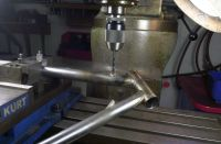 Donald's frame is now mounted on the Bridgeport milling machine to drill the Di2 wire hole in the down tube.  Tube mitre blocks held in the Kurt milling machine vise are used to clamp the down tube.  The tube is rotated and the 6mm drill bit is aligned to perform the drilling.  Better to err on the safe side than to hand drill.