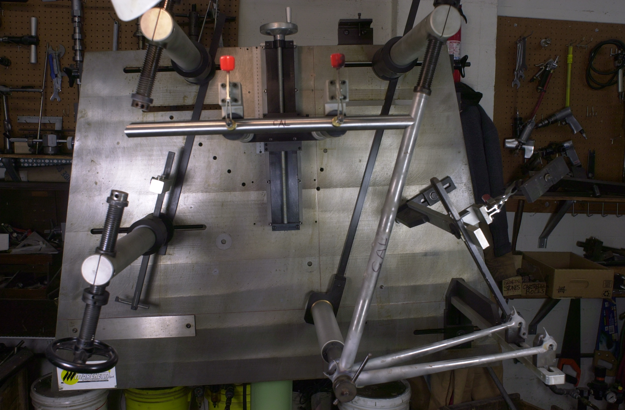 Previously the seat tube and chainstays of the next frame were tacked into the bottom bracket shell then removed from the fixture and completely brazed from the inside of the shell.  Now the frame returns to the fixture and the top tube, which has been mitred on both ends, is positioned.