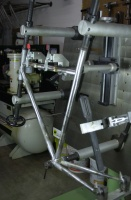 Angle shot of frame no. 7018 held in the ML 301/G-500 Marchetti brazing (welding) fixture.  The frame tubes are held 500mm. from the fixture plate which rotates on an axle through a 100mm. diameter bearing housing.  Rotation of the axle is modulated by a pneumatic brake which facilitates optimal positioning of each joint during the brazing process.